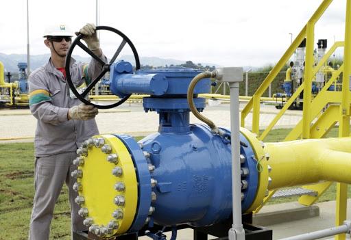 Trabalhador manipulando válvula de gasoduto